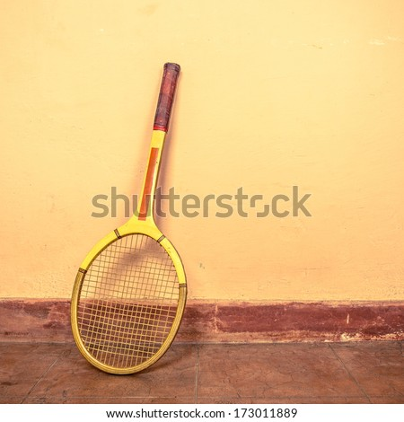 Vintage tennis racket against a wall - stock photo