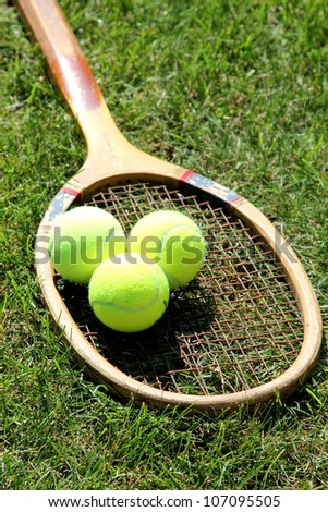 Vintage tennis racket with balls on grass court - stock photo