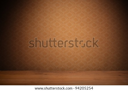 Vintage textured brown wallpaper with heavy vignetting over a wooden floor, empty with copyspace. - stock photo