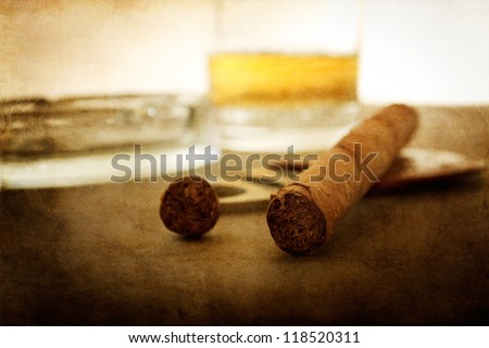 vintage textured cigar wallpaper with whiskey in background - stock photo