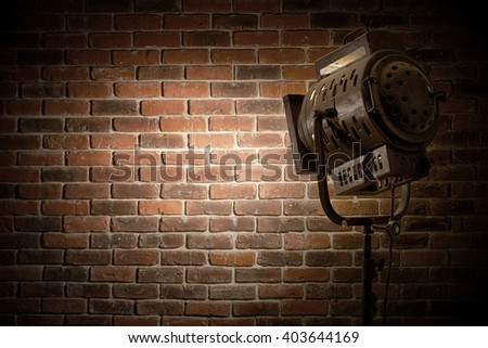 vintage theater / movie spot light focused on a brick wall background - stock photo