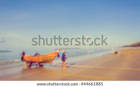 Vintage tone blur image of Fisherman and  small boat on the beach for background usage .