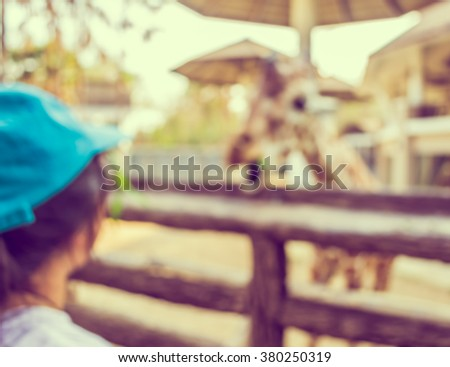 vintage tone blur image of Girl Feeding Giraffe at Zoo for background usage. - stock photo