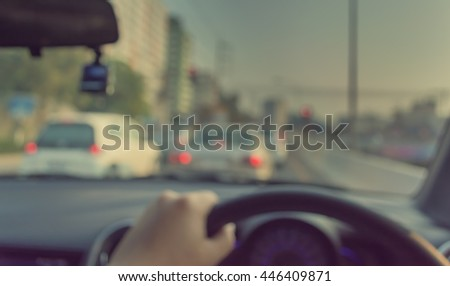 vintage tone blur image of people driving car on day time for background usage.(take photo from inside)