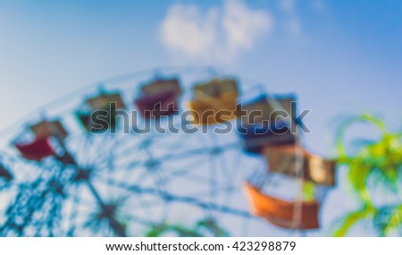 vintage tone blur image of theme park on day time for background usage .