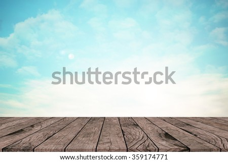 vintage tone color blue sky and clouds background with sunny flare light with aged wood panel perspective:retro wood floorboard line with blurry blue atmosphere backdrop:advertising product on display - stock photo