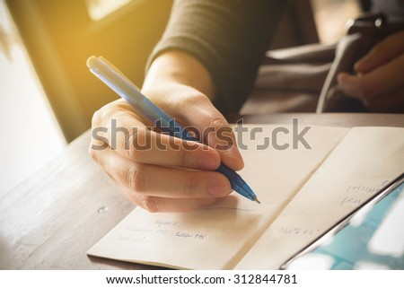 vintage tone Hands of a businesswoman using a pen and reminder  / focus on one point and  shallow depth of field / Background defocus - stock photo