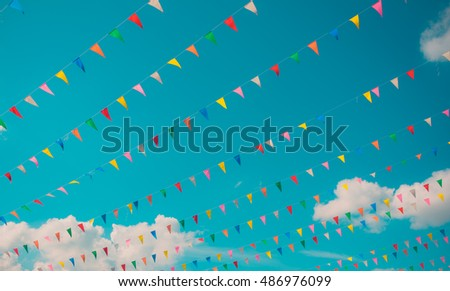 vintage tone image of festival flag line with blue sky in background on day time .
