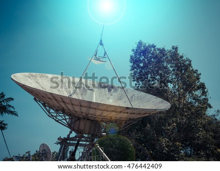 vintage tone image of large satellite dish and blue sky in background .