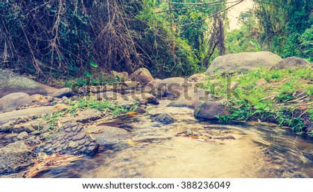 vintage tone long exposure image of river and rock on day time. - stock photo