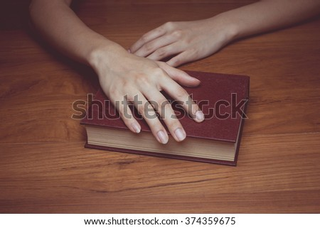 vintage tone of A close-up of a christian woman holding the bible. - stock photo