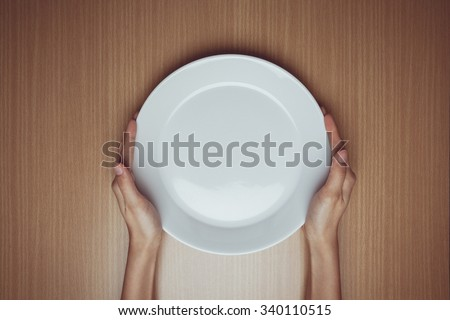 Vintage tone of A female hands hold a empty(blank) white dish(plate) on the wood table(desk), top view at the studio. - stock photo