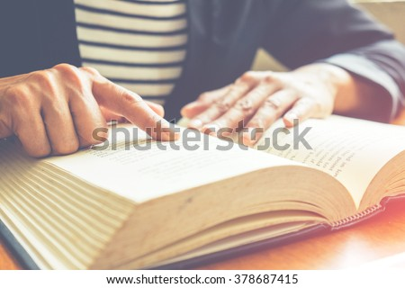 Vintage tone of Asia woman reading book in library .Retro filter effect,soft focus,low light.(selective focus)   - stock photo