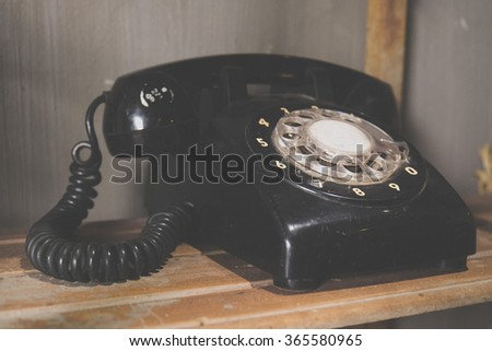 Vintage tone of black phone on old wooden table background - stock photo