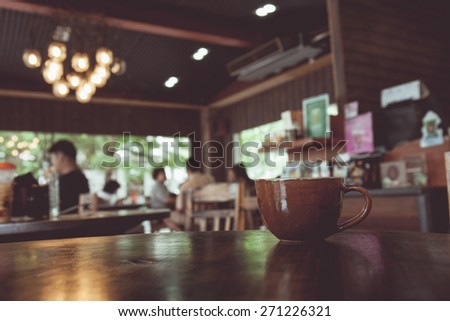 vintage tone of cup of coffee on table in Coffee shop blur background with bokeh image. - stock photo