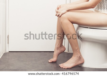 vintage tone of Hand of woman in bath towel sitting on toilet bowl