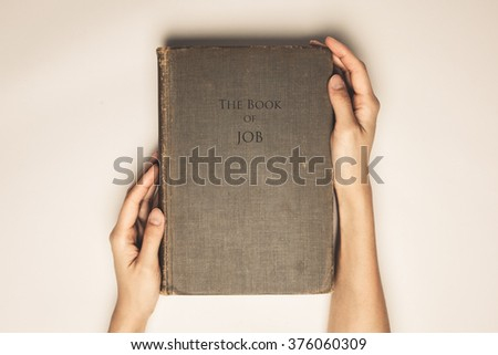 Vintage tone of hands hold the book bible of job - stock photo