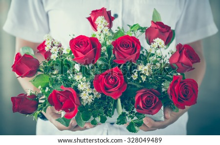 vintage tone of male hand giving bouquet of red roses - stock photo