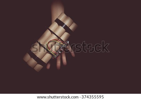 vintage tone of woman hand with the suicide bomb. - stock photo