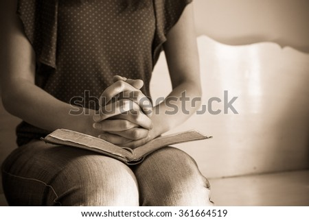 Vintage tone of woman hands on bible. she is reading and praying over bible - stock photo