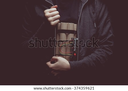 vintage tone of woman in a black jacket strapped with explosives and detonator holds in her hand - stock photo