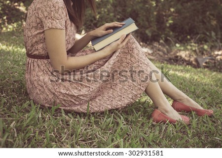 Vintage tone of Young woman reading bible in natural park - stock photo