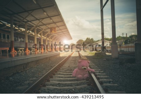 vintage tone, teddy bear sitting alone at the tracks