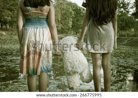 vintage tone two kid standing and hand hold white bear at the swamp - stock photo