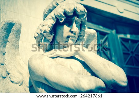 Vintage toned beautiful angel with his arms crossed - stock photo