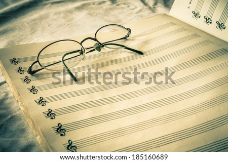 Vintage toned blank composition sheet music with eyeglasses  - stock photo
