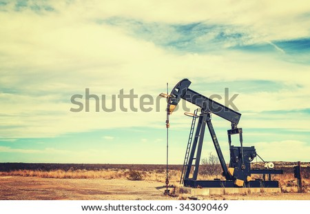 Vintage toned picture of an oil pump jack, Texas, USA. - stock photo