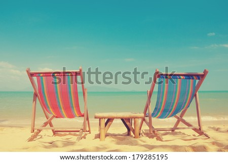 Vintage toned two beach chairs on tropical shore - stock photo
