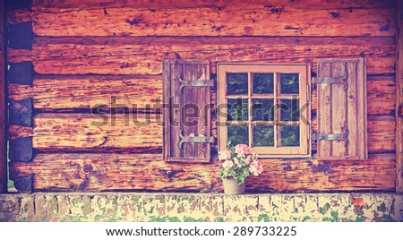 Vintage toned window of old wooden cottage with pot plant. - stock photo
