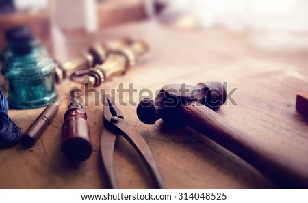 Vintage tools by the window. Old and well used hammer, pliers and screw driver with antique brass drawer handle in background. Intentionally shot in muted vintage tone. Shallow depth of field. - stock photo