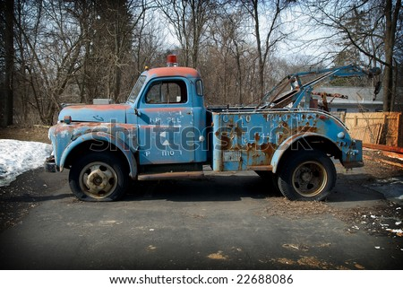 Vintage tow truck in a parking lot - stock photo