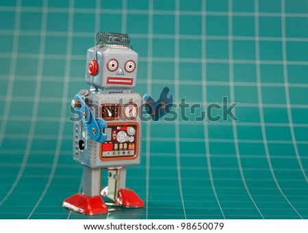 Vintage toy robot on green background - stock photo