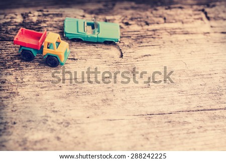 Vintage toy truck and blue car on wooden table background with copy space - stock photo