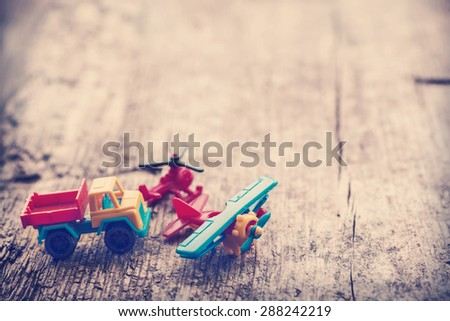 Vintage toy truck, plane with wings and propeller and blue car on wooden table background with copy space - stock photo