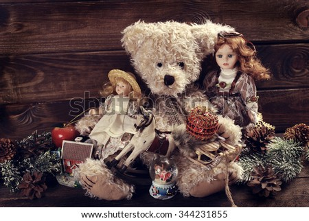 vintage toys like dolls,teddy bear,rocking horse and decorations for christmas gifts  on wooden background - stock photo