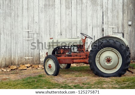 Vintage tractor by barn - stock photo