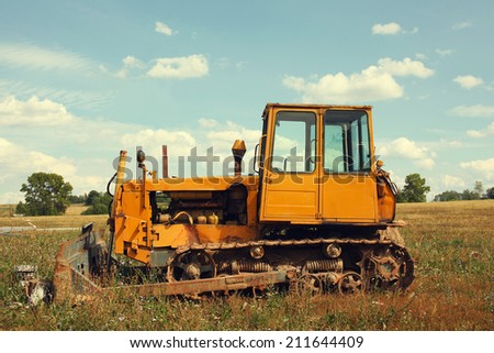 Vintage tractor in field - stock photo