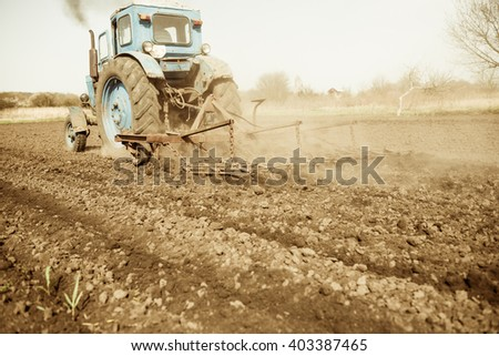 vintage tractor plowing soil on farmland
