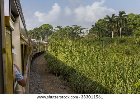 Vintage train that goes from Panama City to Colon is passing rainforest close to Panama Canal. - stock photo