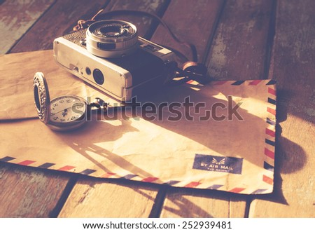 Vintage travel background, old film camera ,antique watches and airmail letter on wood table, instagram effect filter - stock photo