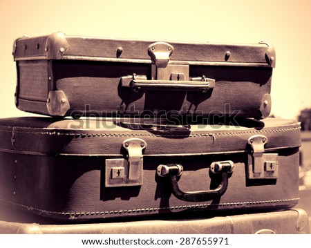 Vintage travel bags. Old suitcases on the road, monochromatic toned color in retro style. Voyage on automobile - old road with classic baggage. Travel concept in nostalgia style on an old photo. - stock photo