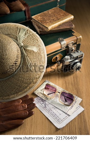 Vintage traveler suitcase with sunglasses, straw hat, old camera and maps. - stock photo