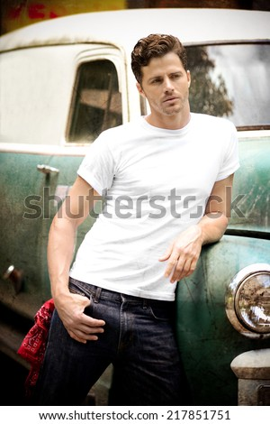 Vintage Truck with Good Looking guy leaning against it - stock photo