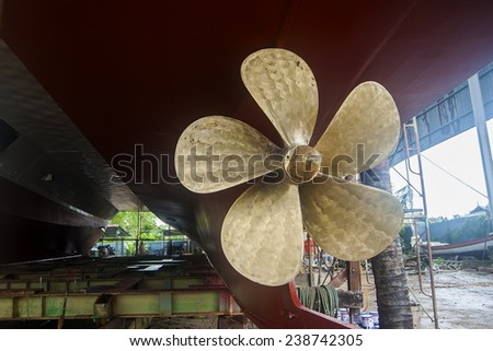 Vintage Tug Brass Propeller Vessel Mounted dry-docked old steam tug boat vessel with solid brass propeller and riveted hull metal plates visible - stock photo