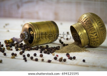 Vintage Turkish pepper mill with sprinkled peppers and ground pepper on a wooden background