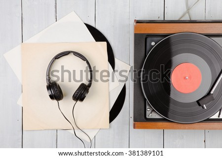 Vintage turntable and headphones on the wooden background - stock photo